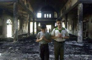 Children pray at their church after arsonists burned it.