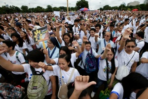 Tens of thousands of protesters flash thumbs down signs during the rally. AP