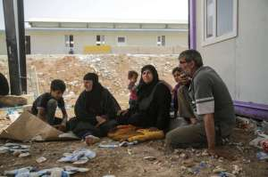 Bushra (centre right) rests with her husband and family members in the shadow of a building in Iraq's Kurdistan region. They walked from their farm near Mosul to a checkpoint near the Kurdistan region's Erbil city. The family fled with almost no belongings. (United Nations High Commissioner for Refugees)