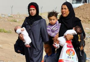 Iraq refugees were seen fleeing Mosul on Thursday en route to the self-ruled northern Kurdish region, as they walk past an area in Irbil, Iraq, 350 kilometers (217 miles) north of Baghdad. AP
