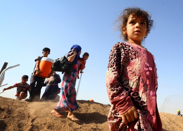 People who fled from the violence in Mosul walk inside the Khazer refugee camp on the outskirts of the Kurdish city of Arbil. Hundreds of Christian families abandoned homes in Mosul to jihadist gunmen as they fled an ultimatum threatening their community's centuries-old presence in the northern Iraqi city. Reuters