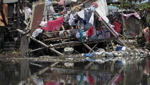 A woman hangs newly laundered clothes at a damaged house after Typhoon Rammasun battered the town for two days, in Rosario, Cavite city, south of Manila July 18, 2014. REUTERS